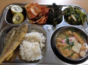 Kiwi, kimchi, pickled greens, greens salad, fish cake soup, and whole fish.