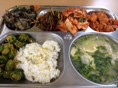 Eggplant salad, kimchi, spicy pork, ssamjang peppers, rice with millet, dumpling and egg soup