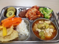 Fried fish, rice, peppers dipped in ssamjang, kiwi, kimchi, soft tofu stew, mini sausages with broccoli